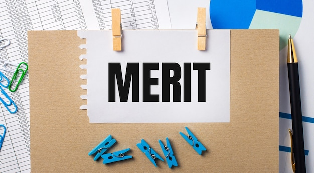 On the desktop are reports, blue clothespins and charts, a pen, a notebook and a sheet of paper with the text merit. business concept
