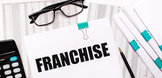 On the desktop are reports, documents, glasses, a calculator, a pen and paper with the text franchise. business concept