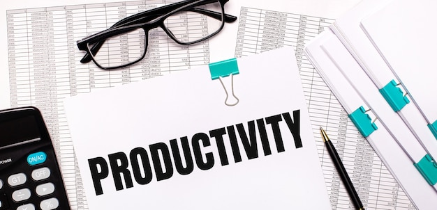 On the desktop are reports, documents, glasses, a calculator, a pen and paper with the text productivity. business concept
