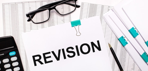 On the desktop are reports, documents, glasses, a calculator, a pen and paper with the text revision. business concept