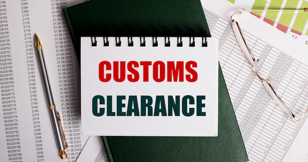 On the desktop are reports, glasses, a pen, a green diary and a white notebook with the words customs clearance. workplace close-up. business concept
