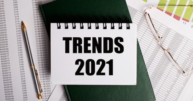 On the desktop are reports, glasses, a pen, a green diary and a white notebook with the words trnds 2021. workplace close-up. business concept