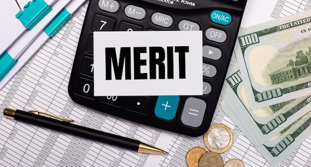 On the desktop are reports, a pen, cash, a calculator and a card with the text merit. business concept