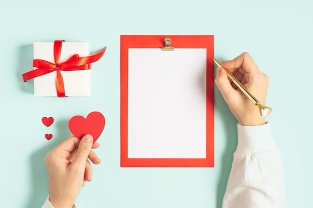 デスクトップの空白のメモ帳。バレンタインギフトと青い作業テーブルの背景に女性の手のフラットレイ