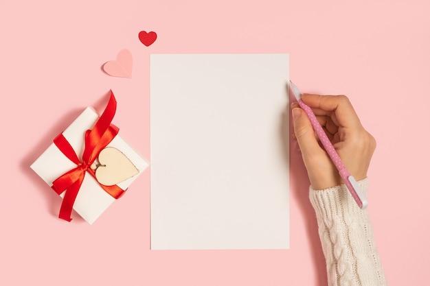 デスクトップの空白のメモ帳。バレンタインギフトとピンクの作業テーブルの背景に女性の手のフラットレイ