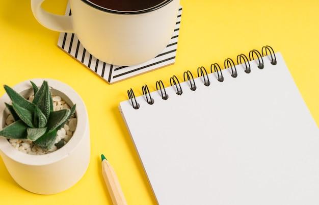 Рабочий стол пустой блокнот с пространством для текста. плоская планировка желтого фона рабочего стола с чашкой чая и растениями.