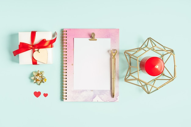 デスクトップの白紙のメモ帳。バレンタインギフトと青いパステルカラーの作業テーブルの背景のフラットレイ
