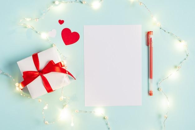 Рабочий стол чистый лист бумаги блокнот. плоская планировка синего фона рабочего стола с подарком на день святого валентина