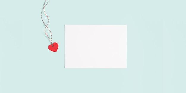 デスクトップの白紙のメモ帳。バレンタインギフトと青い作業テーブルの背景のフラットレイ
