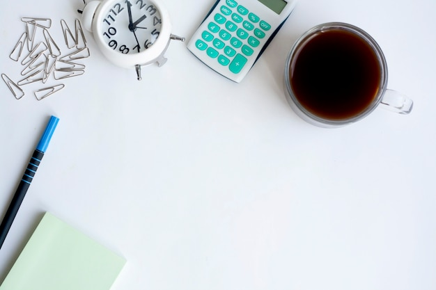Desktop, clock, calculator, note paper, paper clips, pen and coffee on white background, copy space