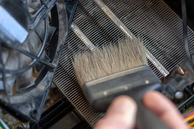 Desktop computer dust cleaning with tassel. cpu cooling radiator system with dust and web.