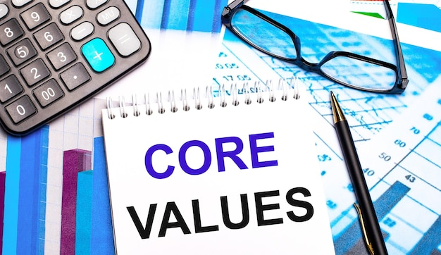 The desktop contains colored tables, a calculator, glasses, a pen and a notebook with the text core values