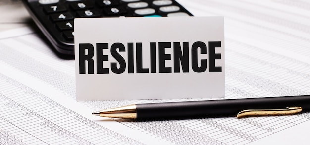 The desktop contains reports, a calculator, a pen, and a white card with the text resilience. business concept