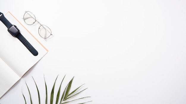Desktop flat lay. notepad, watches, glasses and palm on a white background. copyspace.