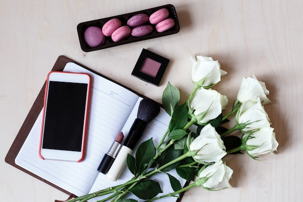 Desktop flatlay with mobile phone, notebook, macaroons, white roses, lipstick, make up brush and blush on wood