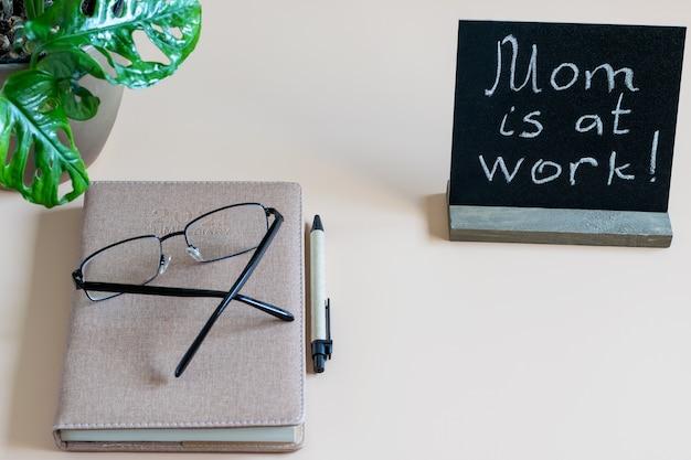 Рабочий стол, домашнее рабочее место с дневником времени, ручкой, очками для глаз и черным бланком с надписью «мама на работе». концепция удаленной работы дома.