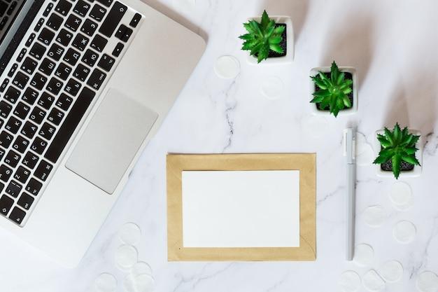 デスクトップアイテム:ノートパソコン、紙カード、机の上に横たわる多肉植物。上面図