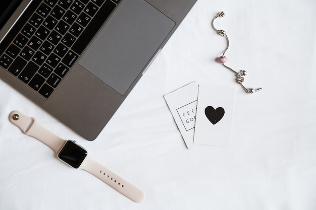 Desktop items: laptop, smart watch, woman accessories, top view
