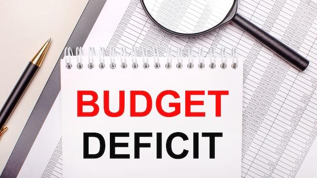 Настольная лупа, отчеты, ручка и блокнот с текстом дефицит бюджета. бизнес-концепция