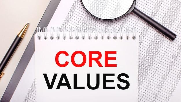 Настольная лупа, отчеты, ручка и блокнот с текстом основные ценности. бизнес-концепция