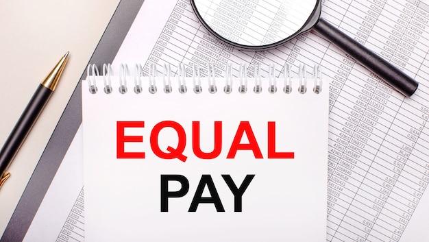 Настольная лупа, отчеты, ручка и блокнот с текстом equal pay. бизнес-концепция