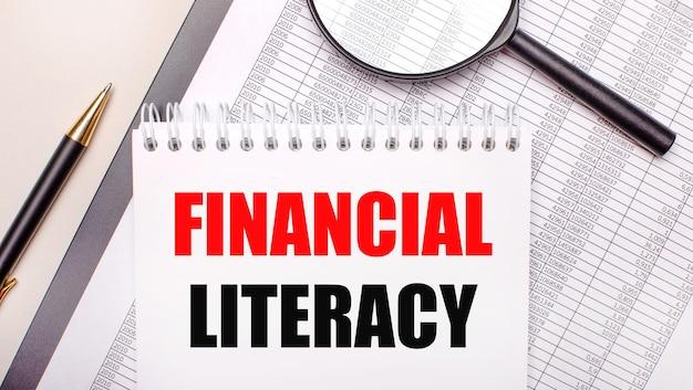 Настольная лупа, отчеты, ручка и блокнот с текстом финансовая грамотность. бизнес-концепция