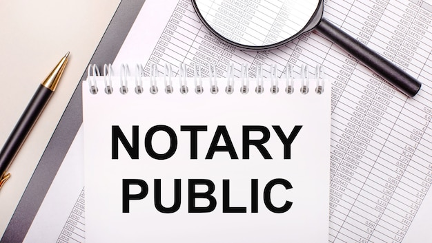 Desktop magnifier, reports, pen and notebook with text notary public. business concept