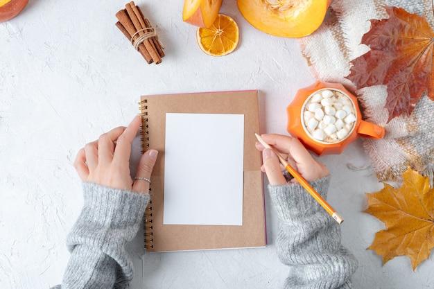 Настольный макет планировщика композиции вид сверху с женскими руками в свитере с тыквами и чашкой кофе