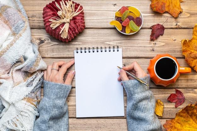 Настольный макет планировщика с руками и осенними листьями