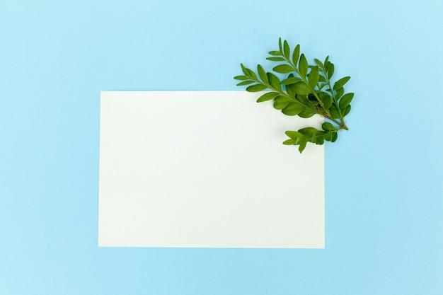 空白の紙カードを使ってデスクトップモックアップ、ぼろぼろの白いテーブル背景に枝空きスペース。スタイルストックフォト、webバナー。フラットレイ