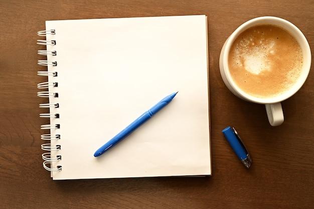 Рабочий стол. блокнот, синяя ручка и подставка под чашку кофе на деревянном столе.