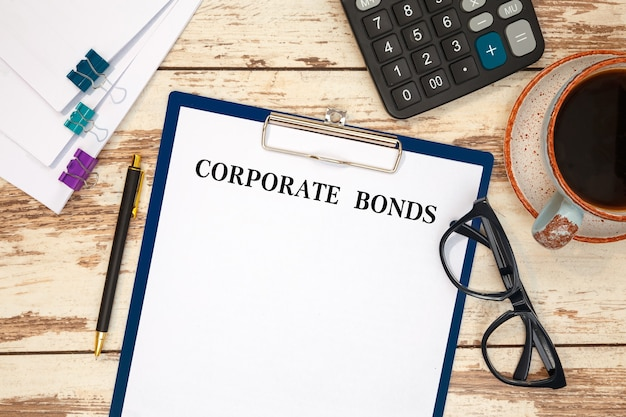Desktop office desk, notebook, glasses, pen and documents with corporate bonds on a table