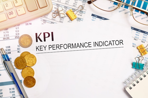 Desktop office desk, notebook, glasses, pen and documents with kpi key performance indicator on a tabl