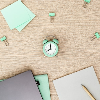 Desktop for student or freelancer. working space. workplace with grey modern laptop, copybook and clock for time control on light table. flat lay.