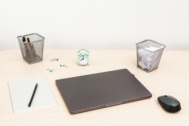 Desktop for student or freelancer. working space. workplace with grey modern laptop, copybook and clock for time control on light table. selective focus.