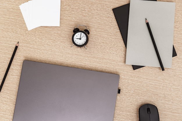 Desktop for student or freelancer. working space. workplace with grey modern laptop, cup of coffee, glasses and clock for time control on light table. flat lay.