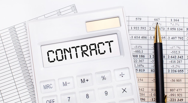 On the desktop there are reports, a white calculator with the text contract on the scoreboard and a pen. business concept.