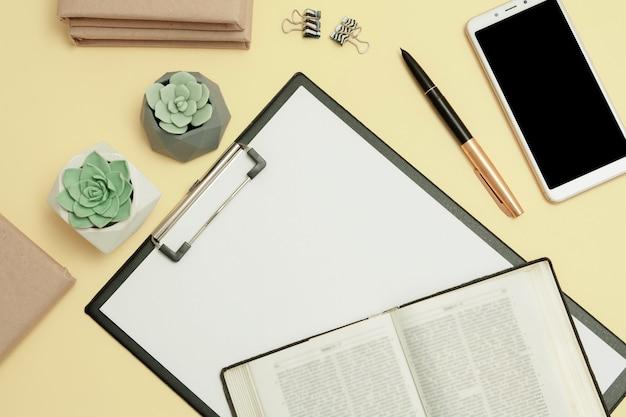 ノート用の聖書とクリップボードを備えたデスクトップ。聖書研究のコンセプト