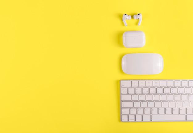키보드, 무선 헤드폰 및 2021 년 배경 색상의 마우스가있는 데스크탑. 노란색 조명