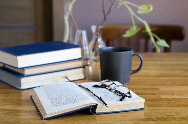 開いた本、本の山、一杯のコーヒーのあるデスクトップ。