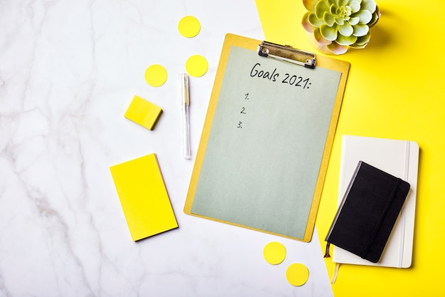 목표 목록 모형 및 사무용품이있는 클립 보드가있는 바탕 화면. 홈 오피스, 계획 목표 설정 개념. flatlay, 평면도