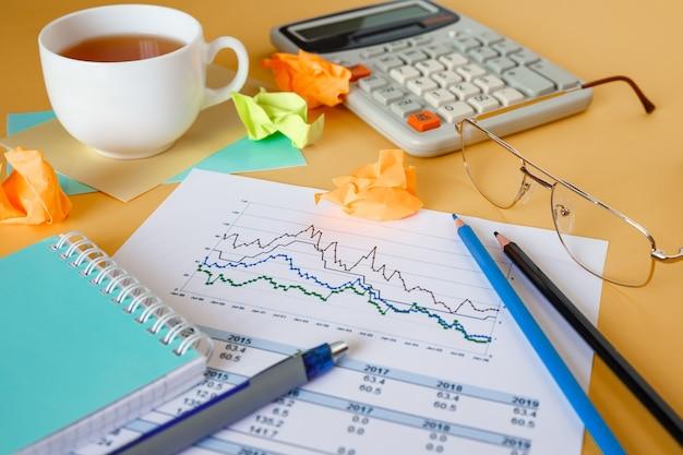 Рабочий стол с документами, калькулятором и блокнотом. документы с графиком износа.