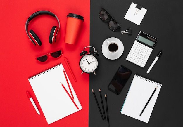 Desktop with earphones, alrm clock, phone, pens, pencils, note, coffee isolated on red and black