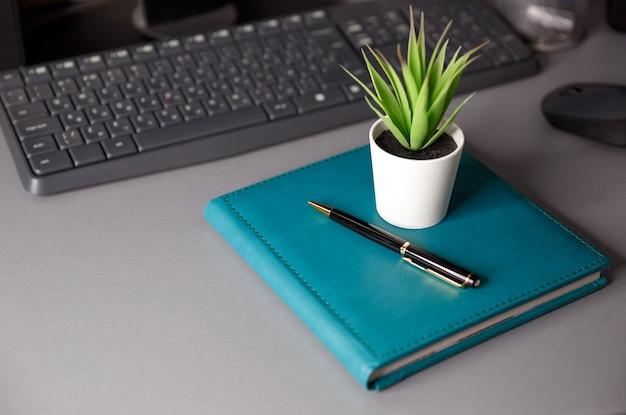 노트북, 키보드, 컴퓨터 마우스, 실내 식물 및 펜이있는 데스크탑. 원격 근무, 프리랜서, 재택 근무의 개념. 집에서 회사 직원의 직장. 텍스트를위한 공간