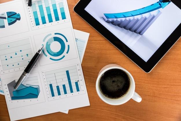 最新のデジタルタブレットで成功したビジネスレポートを備えたデスクトップ、