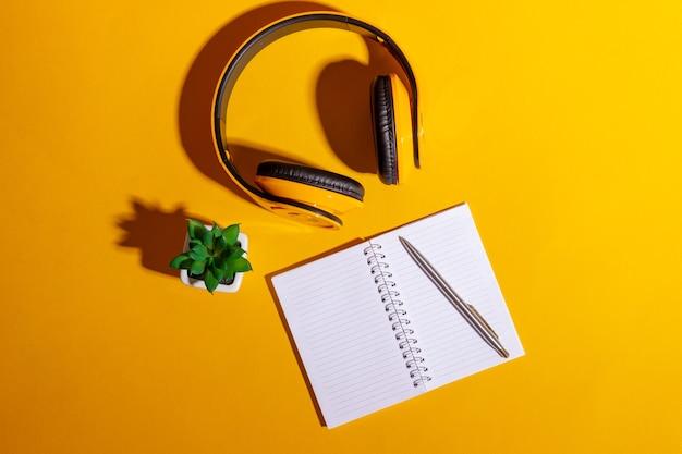 黄色のワイヤレスヘッドフォンと明るい黄色の背景に開いたノートブックを備えたデスクトップ。