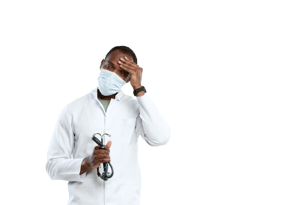Отчаяние, усталость. мужской молодой врач со стетоскопом и лицевой маской на белой студии.