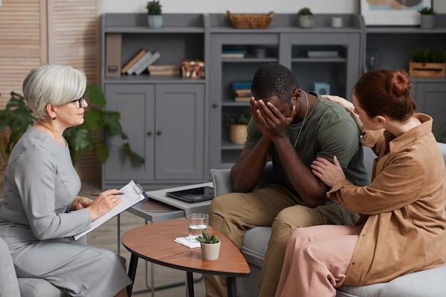心理療法で妻と一緒に座って心理学者と話している絶望したアフリカ人男性