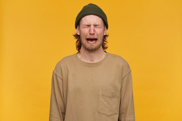 Отчаявшийся мужчина, плаксивый парень со светлыми волосами, бородой и усами. в зеленой шапке и бежевом свитере. плачет с закрытыми глазами и чувствует себя безнадежным. стенд изолирован над желтой стеной