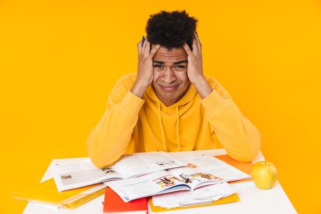 黄色の壁に隔離された教科書と机に座って勉強している絶望的な10代の少年